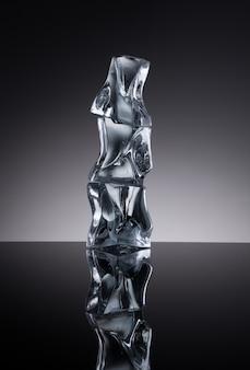 Três cubos de gelo com água no fundo do espelho