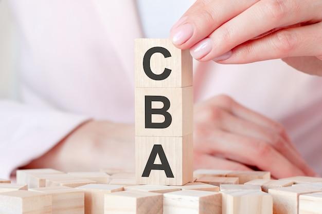 Três cubos de madeira com as letras cba - significa análise de custo-benefício