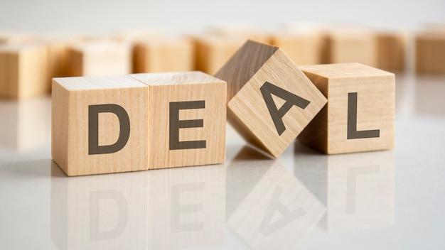 Três cubos de madeira com as letras deal na superfície brilhante de uma mesa cinza. a inscrição nos cubos é refletida na superfície da mesa. conceito de negócios.