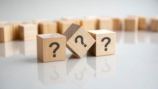 Três cubos de madeira com pontos de interrogação sobre um fundo cinza com espaço de cópia.