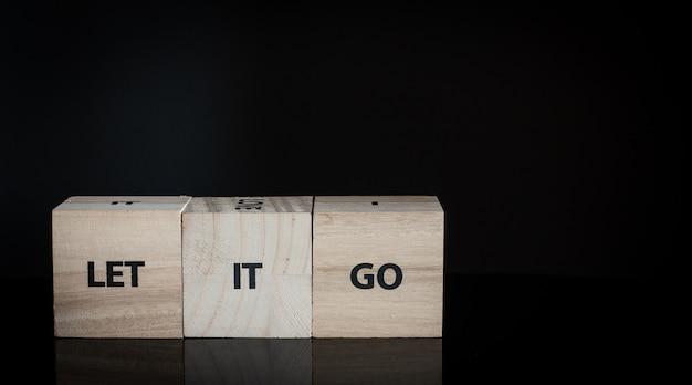 Três cubos de madeira em uma fileira - deixe ir