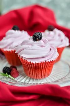 Três cupcakes rosa com amoras no topo