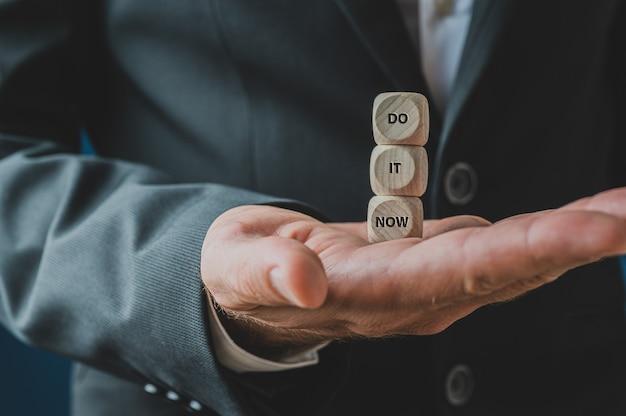 Três dados de madeira empilhados na palma da mão de um empresário carregando uma placa de faça agora.