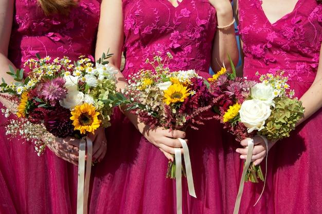 Três damas de honra em vestidos de renda lilás com buquês de flores frescas, foco seletivo