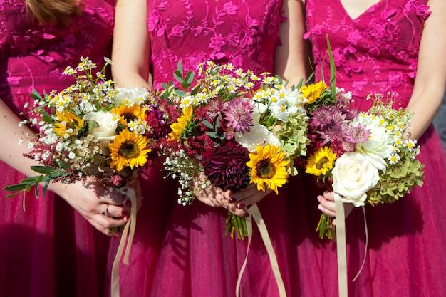 Três damas de honra em vestidos de renda lilás com buquês de flores frescas