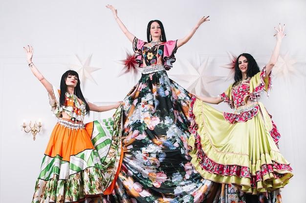 Três dançarinas com vestidos tradicionais ciganas