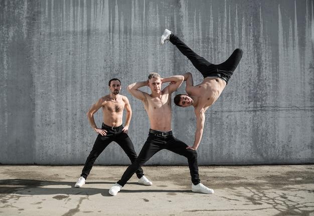 Três dançarinos de hip hop sem camisa posando juntos