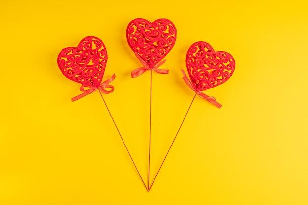 Três decorações para casa em forma de coração esculpido em vermelho sobre fundo amarelo vibrante
