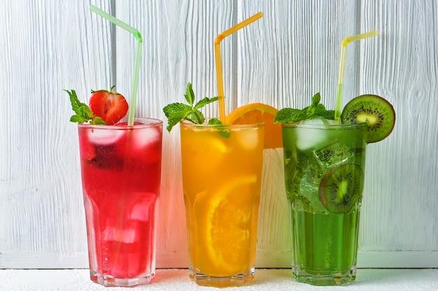 Três deliciosas garrafas de limonada gelada e coloridas brilhantes de kiwi, laranja e morango com hortelã contra a superfície de uma parede de madeira branca