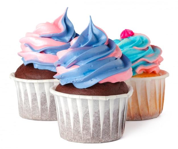 Três deliciosos cupcakes com cobertura de creme, isolados no branco