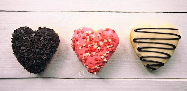 Três deliciosos donuts em forma de coração na mesa de madeira