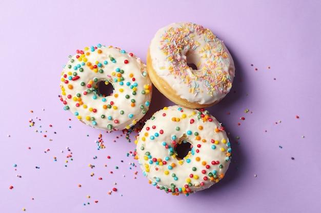 Três deliciosos donuts em fundo violeta, vista de cima