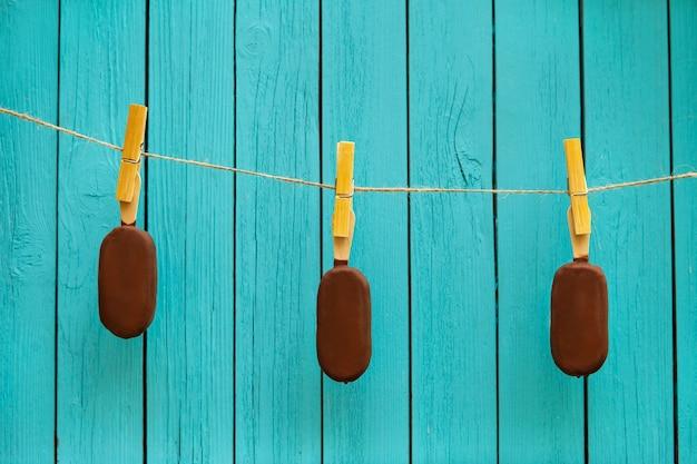 Três deliciosos sorvetes de chocolate na corda perto de fundo turquesa. conceito de comida de verão