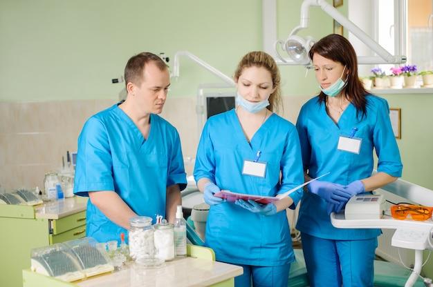 Três dentistas olhando para a pasta na clínica de estomatologia