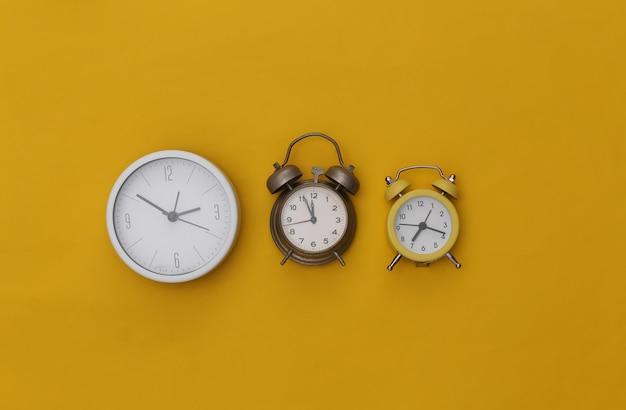 Três despertadores em fundo amarelo.