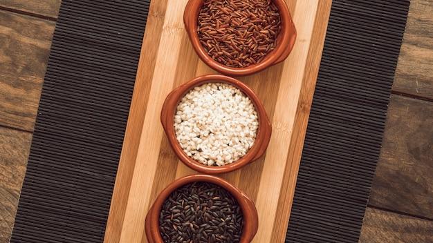 Três, diferente, tipo, de, grão arroz, tigelas, ligado, placemat, sobre, a, tabela madeira