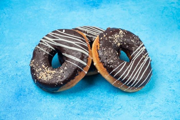 Três donuts de chocolate isolados na superfície azul.