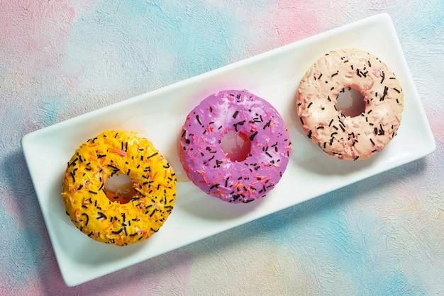 Três donuts em um prato - vista superior