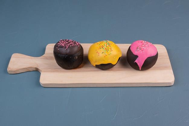 Três donuts na placa de madeira.