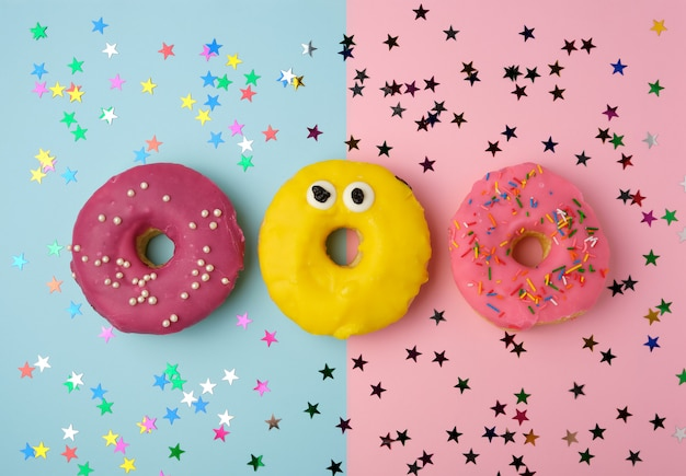 Três donuts redondos em um fundo colorido, banana e com bagas