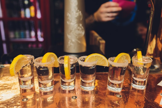 Três doses de tequila com limão e sal em fundo de madeira.