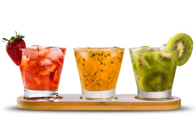 Três drinks feitos com caipirinha de maracujá, morango e kiwi