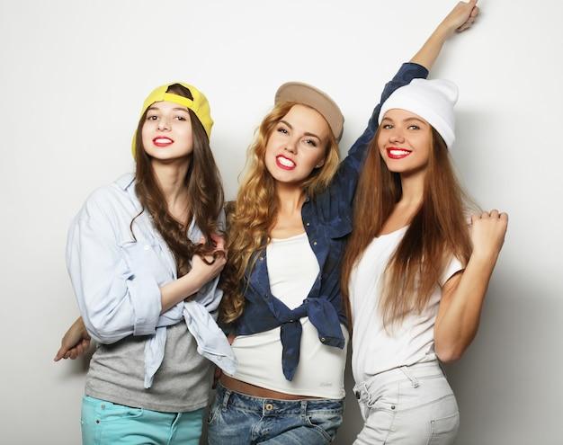 Três elegantes melhores amigos de meninas hippie sexy. ficar juntos e se divertir. sobre um fundo cinza.