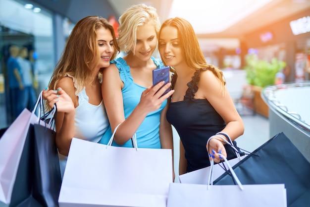Três elegantes mulheres segurando sacolas de compras e olhando no celular depois de fazer compras
