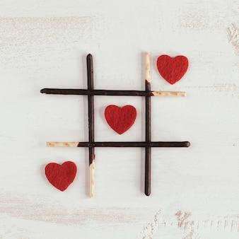 Três em linha com corações vermelhos
