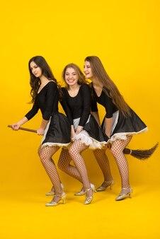 Três empregadas sexy em uma vassoura, bruxas, espíritos malignos.