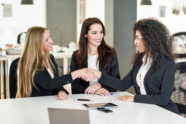 Três empresárias apertando as mãos em um escritório moderno