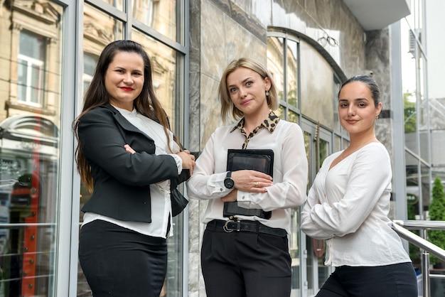 Três empresárias com tablets do lado de fora do prédio e olhando pela câmera
