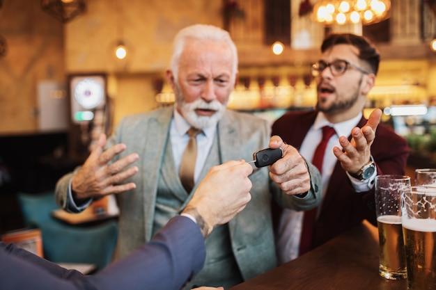 Três empresários comemorando trabalho bem-sucedido no restaurante. um homem tirando a chave do carro de seu parceiro de negócios bêbado.