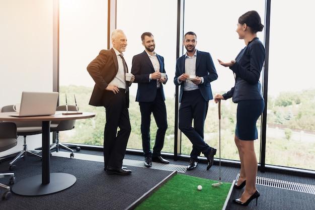 Três empresários e senhoras de negócios jogam golfe.