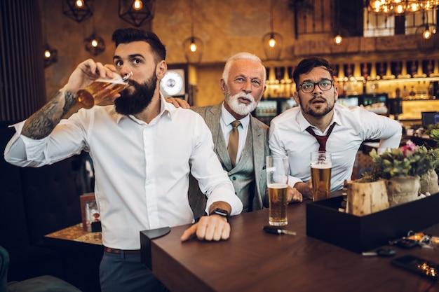 Três empresários torcendo enquanto assistia a uma partida de futebol em um café-bar.