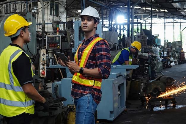 Três engenheiros do sexo masculino planejando produzir peças automotivas com máquinas em uma fábrica na tailândia.