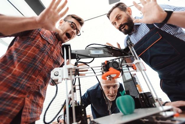 Três engenheiros estão satisfeitos em ver como a impressora 3d é impressa.