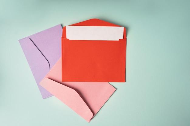 Três envelopes coloridos sobre fundo azul. composição de estilo minimalista, vista superior, conceito de correio