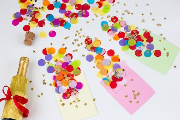 Três envelopes em um fundo branco, confetes coloridos estão voando deles, uma garrafa de champanhe