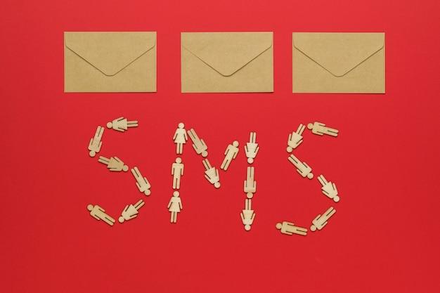 Três envelopes postais de papel e uma inscrição de sms feita de homens de madeira sobre um fundo vermelho. o conceito de comunicação entre pessoas.