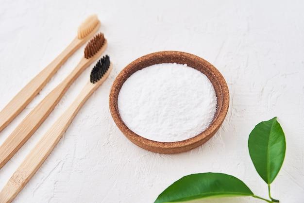 Três escovas de dente de bambu de madeira e bicarbonato de sódio