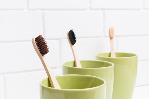 Três escovas de dente em três copos verdes diferentes em uma superfície branca