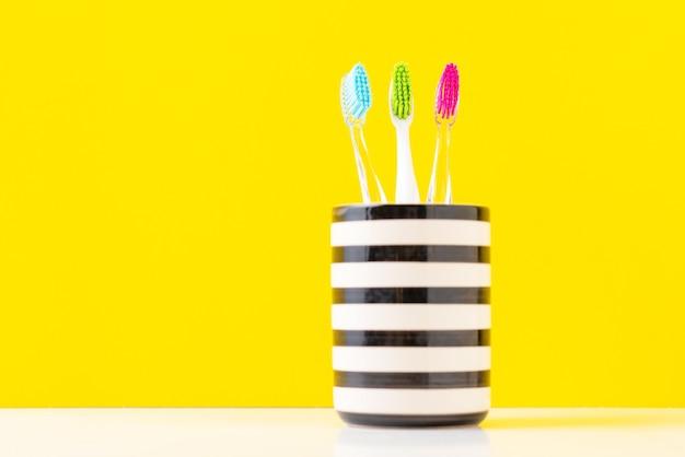 Três escovas de dentes coloridas plásticas no vidro em um fundo amarelo, fim acima