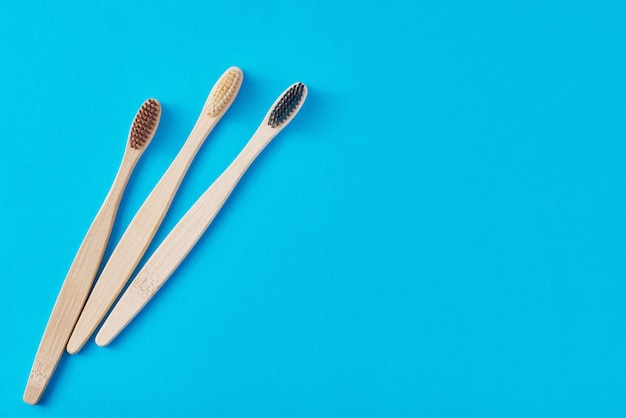Três escovas de dentes de bambu de madeira em um fundo azul, vista superior. conceito de atendimento odontológico