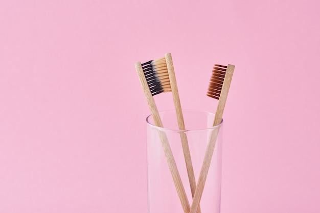 Três escovas de dentes de bambu de madeira em vidro em um fundo rosa. conceito de higiene de atendimento odontológico