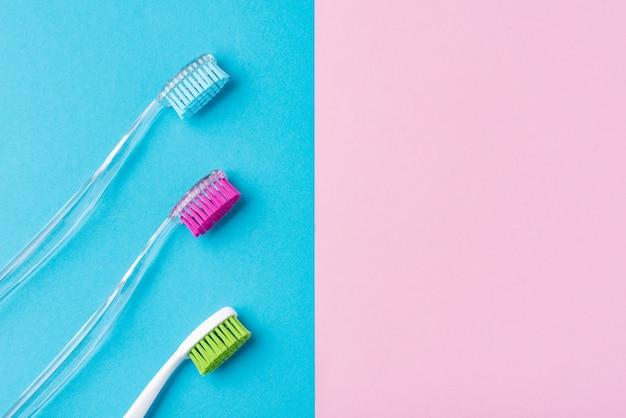 Três escovas de dentes de plástico em um colorido azul e rosa