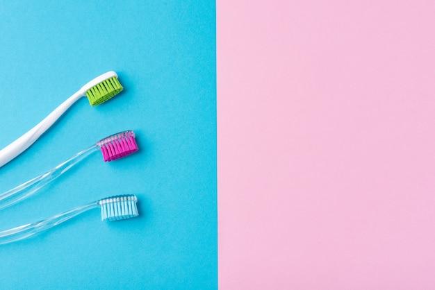 Três escovas de dentes de plástico em um fundo colorido de azul e rosa, close-up