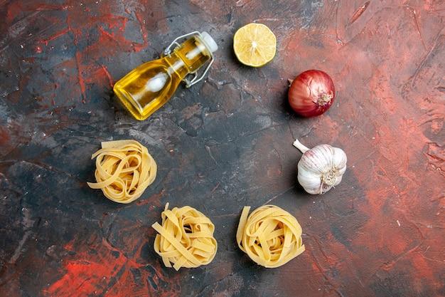 Três espaguetes e massas de borboleta cozidos, cebola, limão, alho e garrafa de óleo em fundo de cor mista
