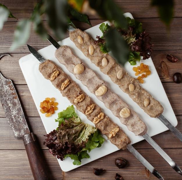 Três espetos de purê de nozes, amendoim, mistura de amêndoa