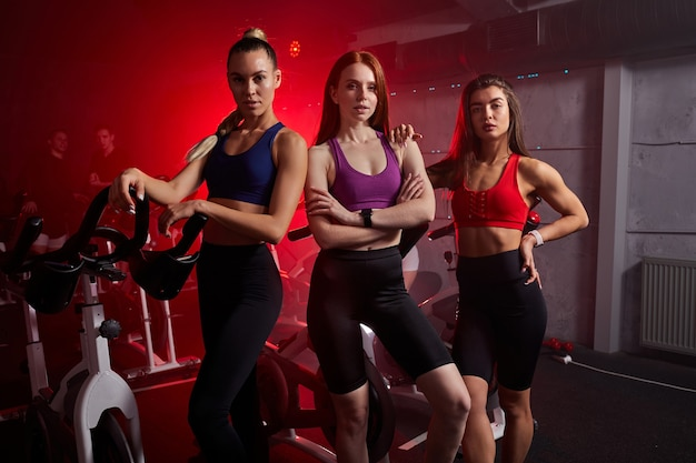 Três esportistas em forma estão juntas perto de bicicletas ergométricas no ginásio, posando. isolado em um espaço iluminado por néon vermelho na parede
